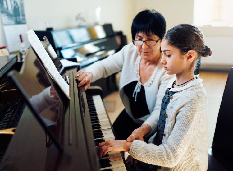 Woman Teaching Girl How To Play Piano